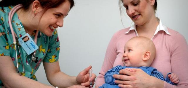 Nurse vaccinates smiling baby.